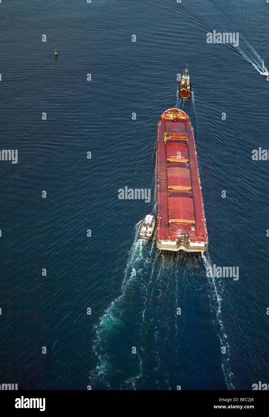 large red barge being guided by tug boats in ocean - Stock Image