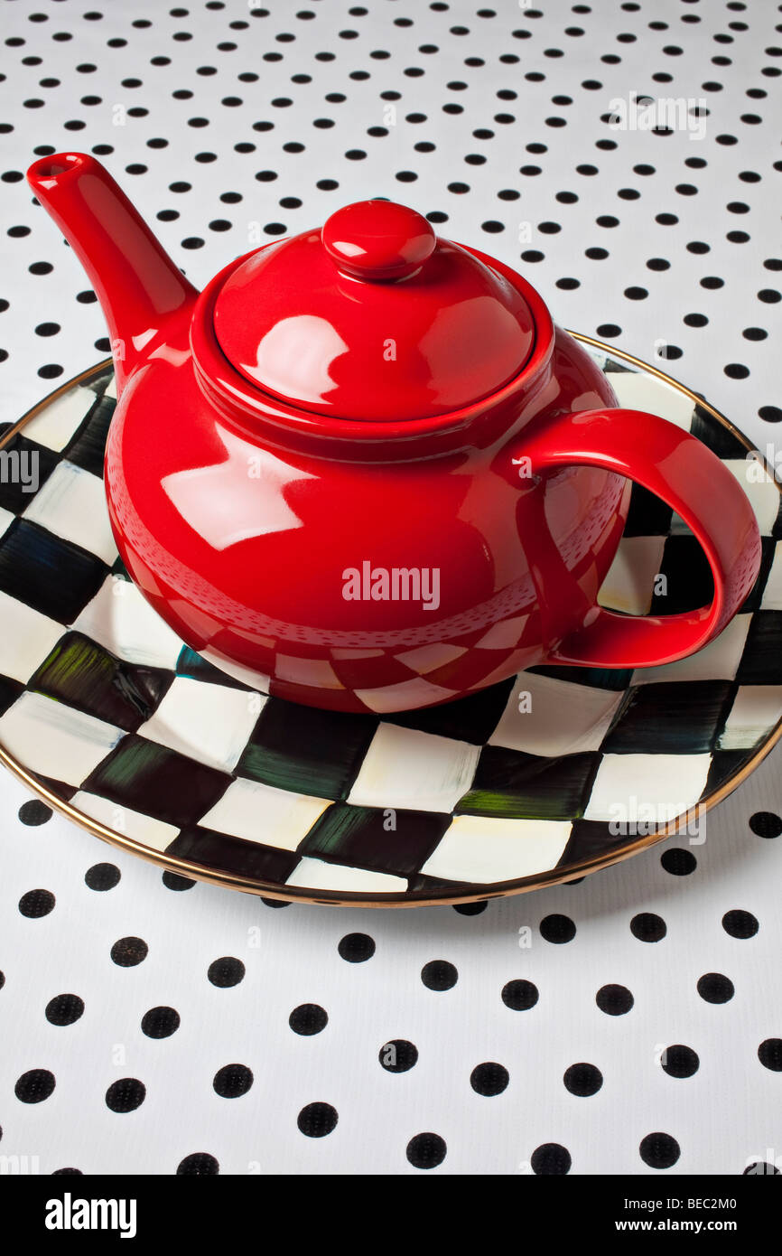 Red teapot on checkerboard plate - Stock Image
