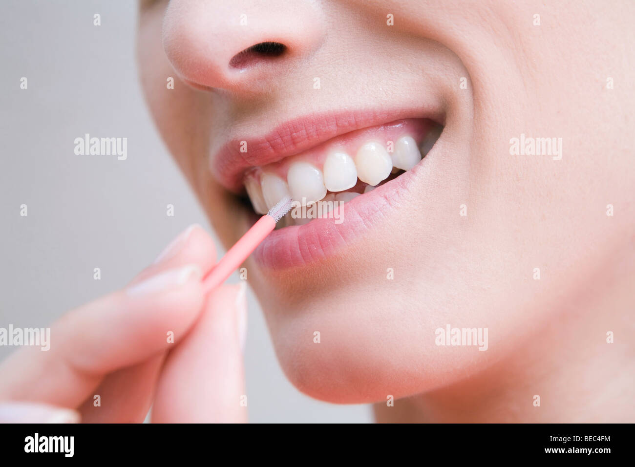 Woman cleaning teeth with interdental brush. - Stock Image