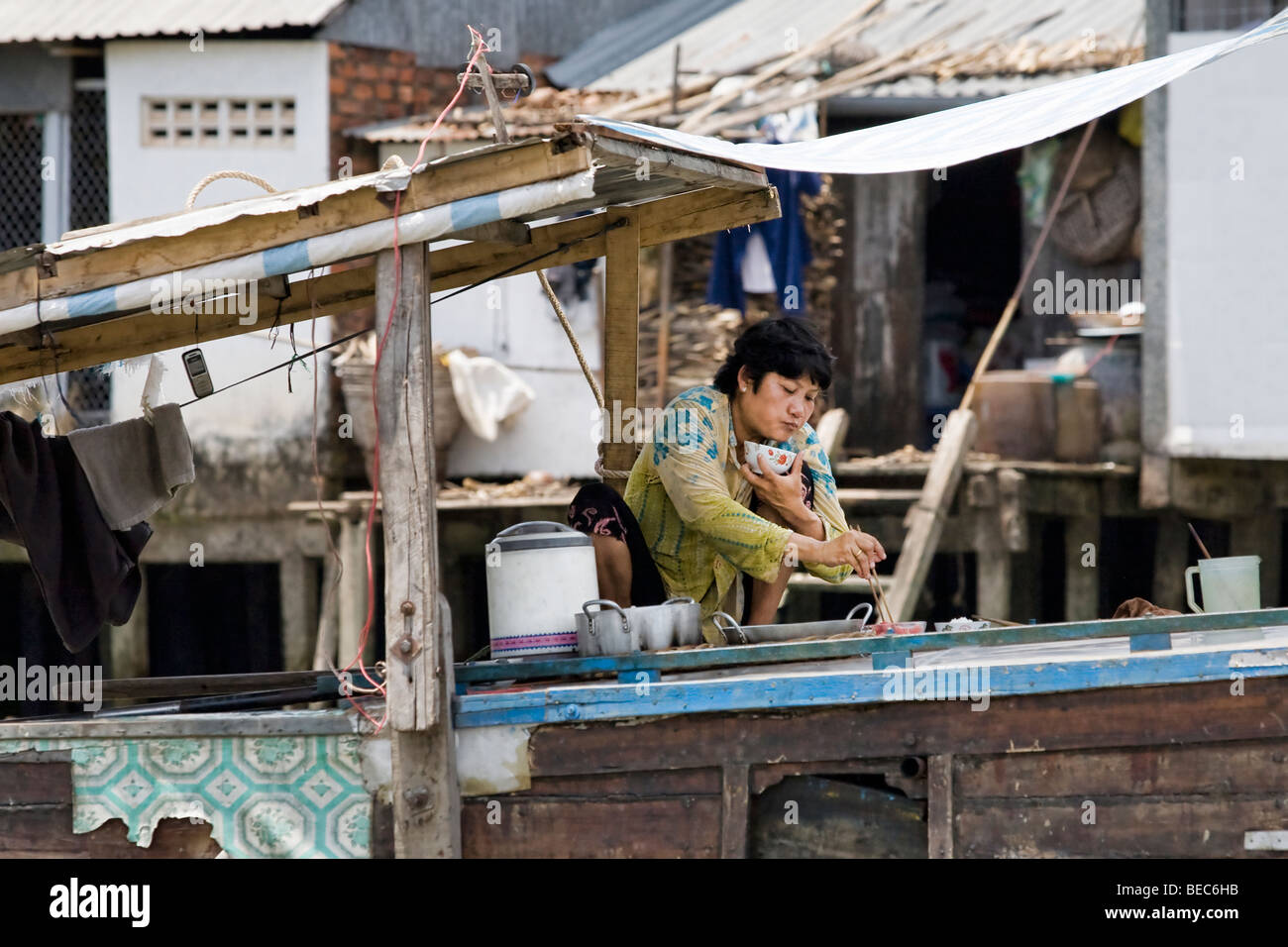 A woman eating on a houseboat on the Mekong Delta, Vietnam Stock Photo