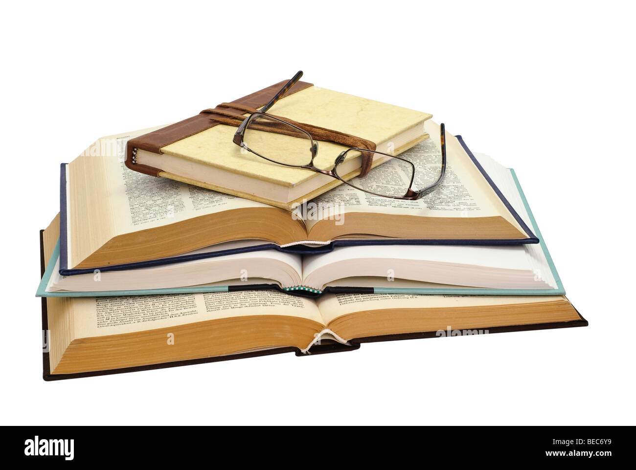 glasses on a stack of four books , one closed and three open, on white background, saved with clipping path - Stock Image