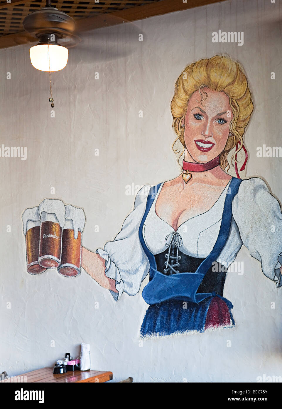 Painted mural of German woman serving beer on wall of cafe bar Fredericksburg Texas USA - Stock Image
