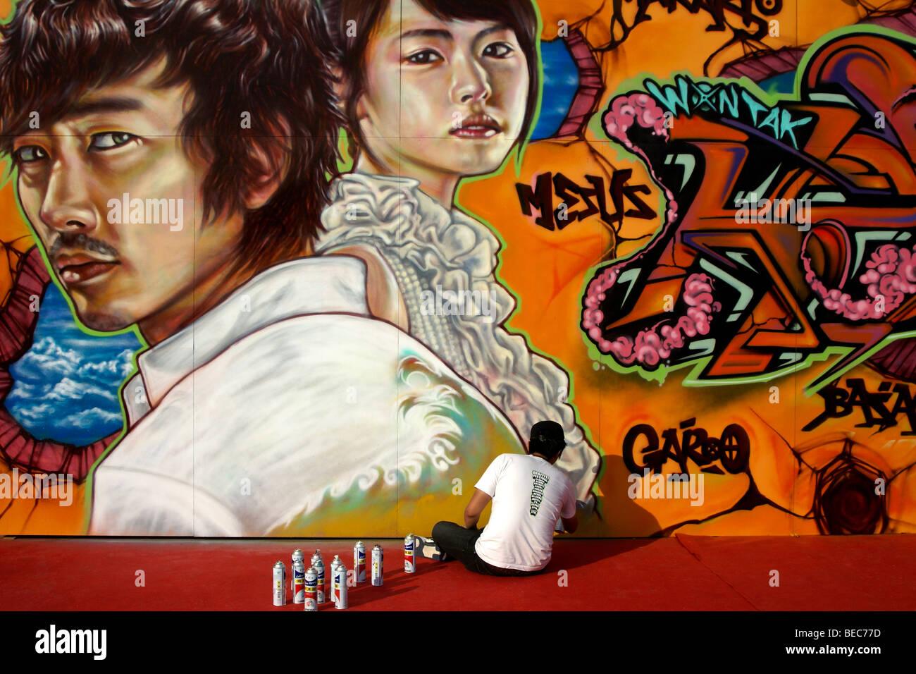 Artist painting mural at Graffiti Festival, Jinju Fortress, South Korea - Stock Image
