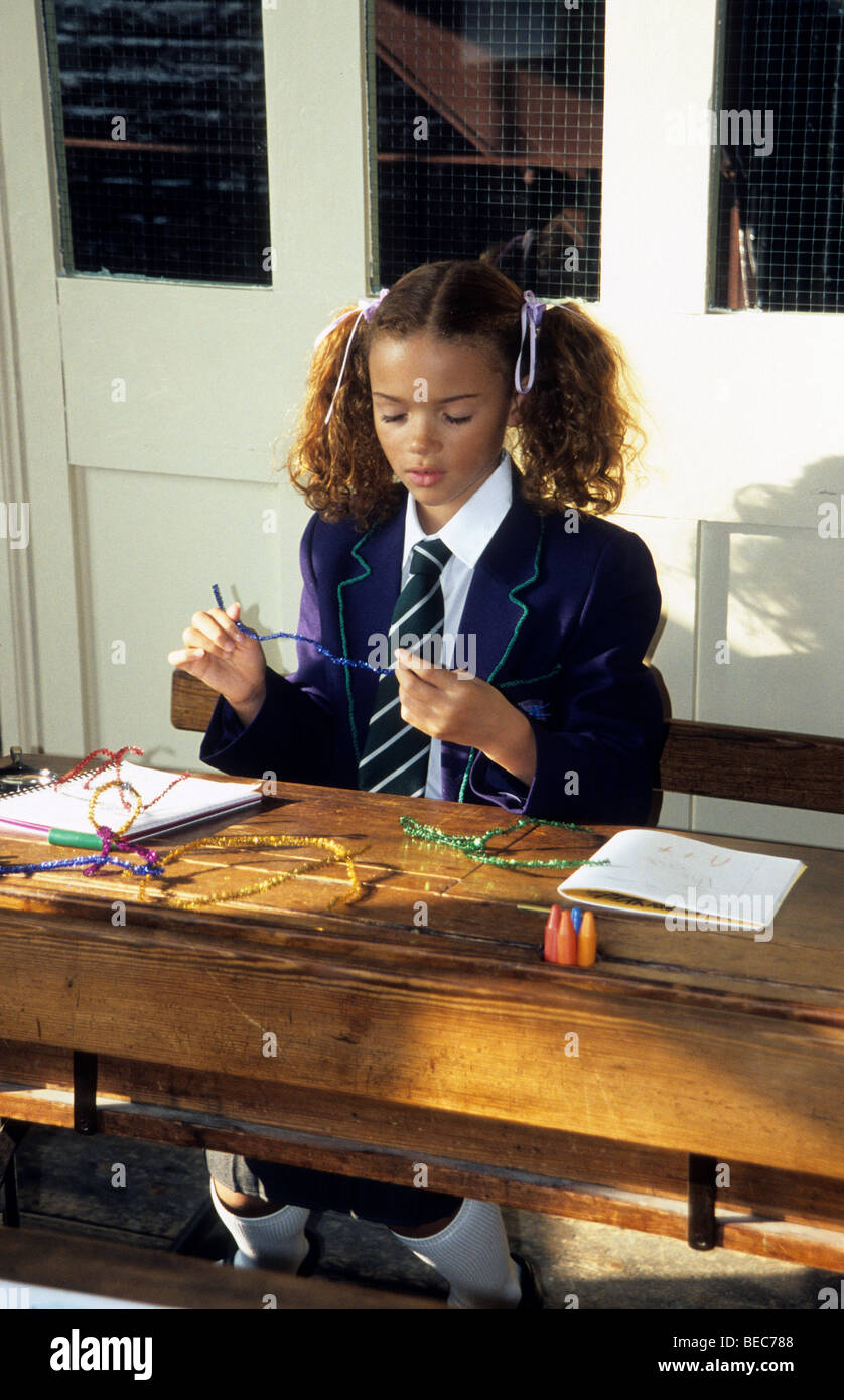 Schoolgirl with pigtails doing crafts at her desk. - Stock Image