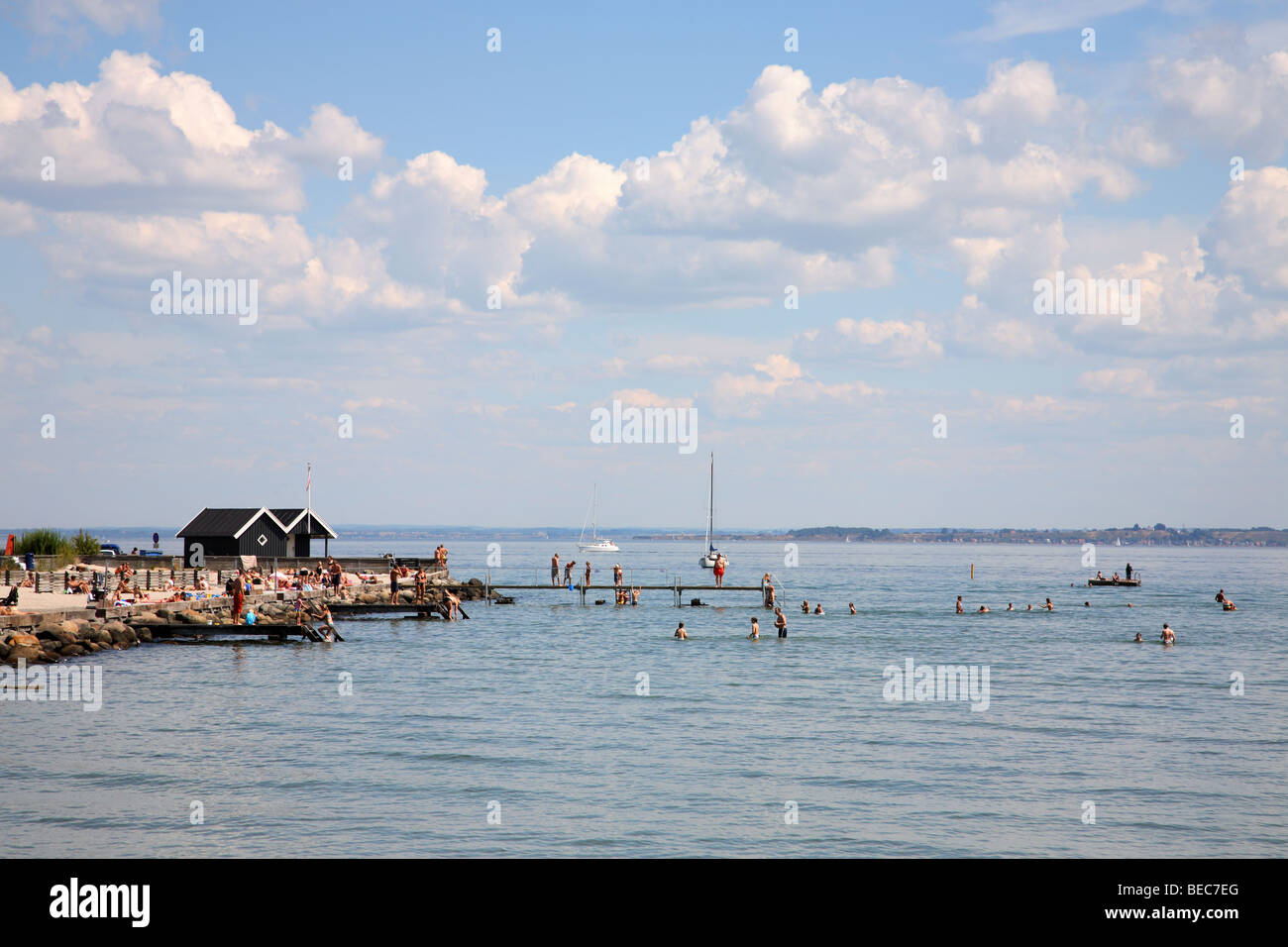 One summer day on the Danish beach at Rungsted Kyst. The Swedish island Ven can be seen across the Sound in the - Stock Image