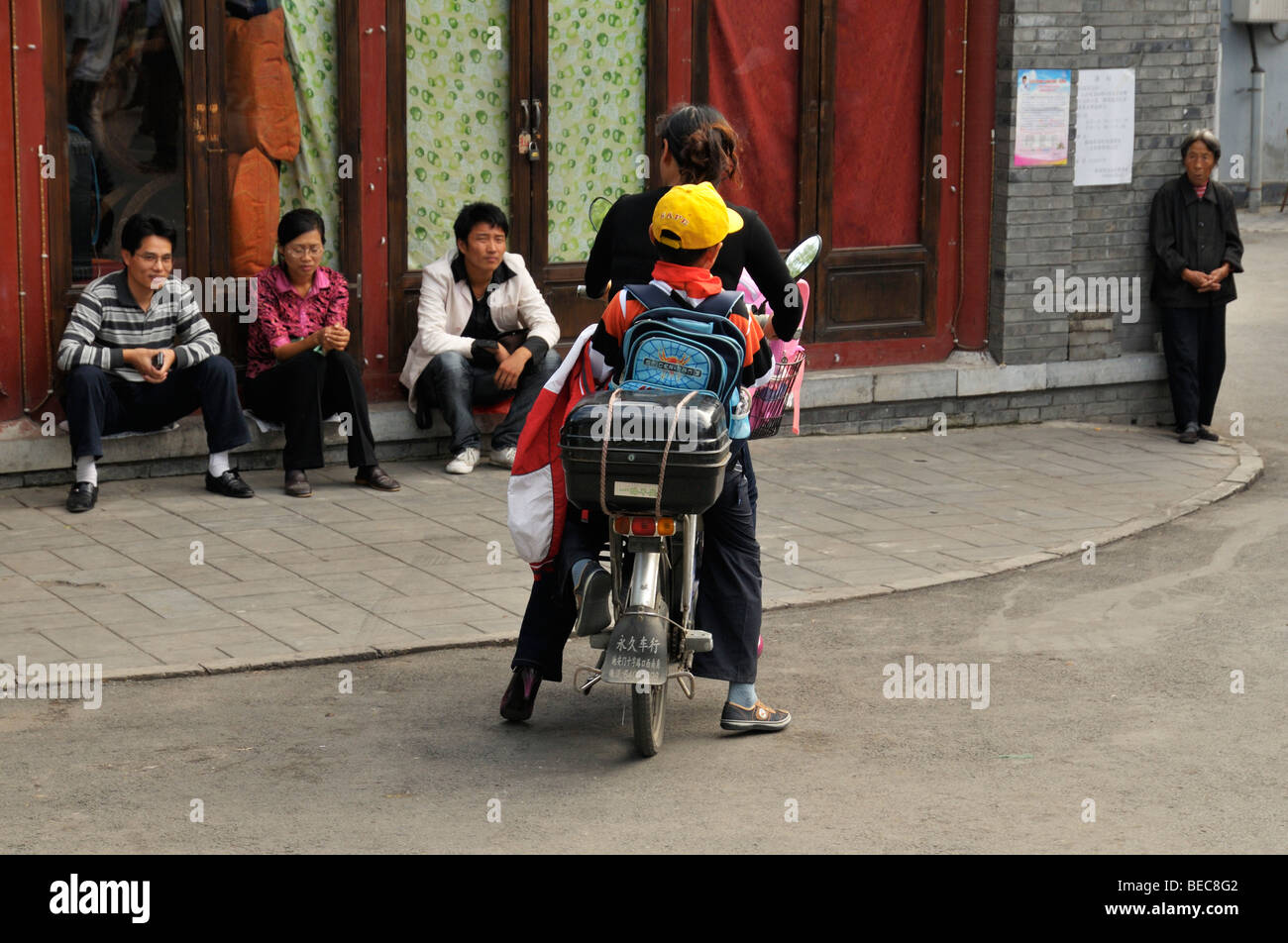 Chinese woman with young boy on a motorbike returning home, Shichahai CN - Stock Image