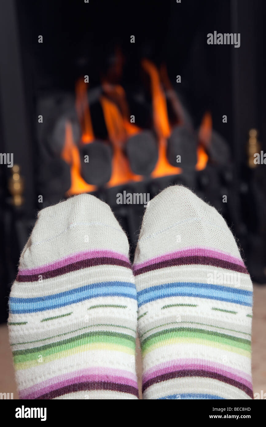 A woman's feet in a pair of stripy warm wool socks warming in front of a cosy coal gas fire with hot coals at - Stock Image