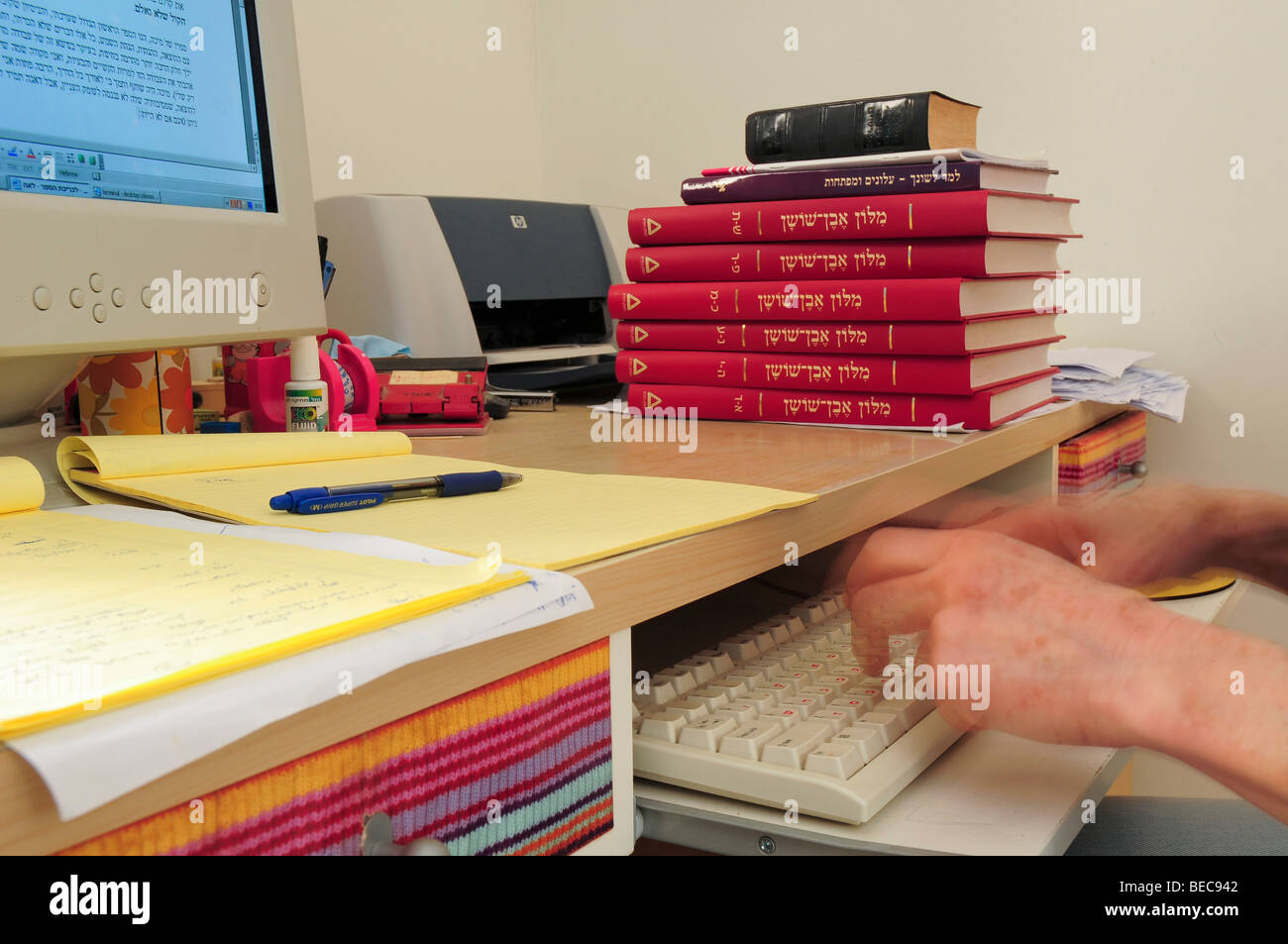 Female Copy-Editor working in front of a computer editing an academic paper with the aid of a dictionary and other - Stock Image
