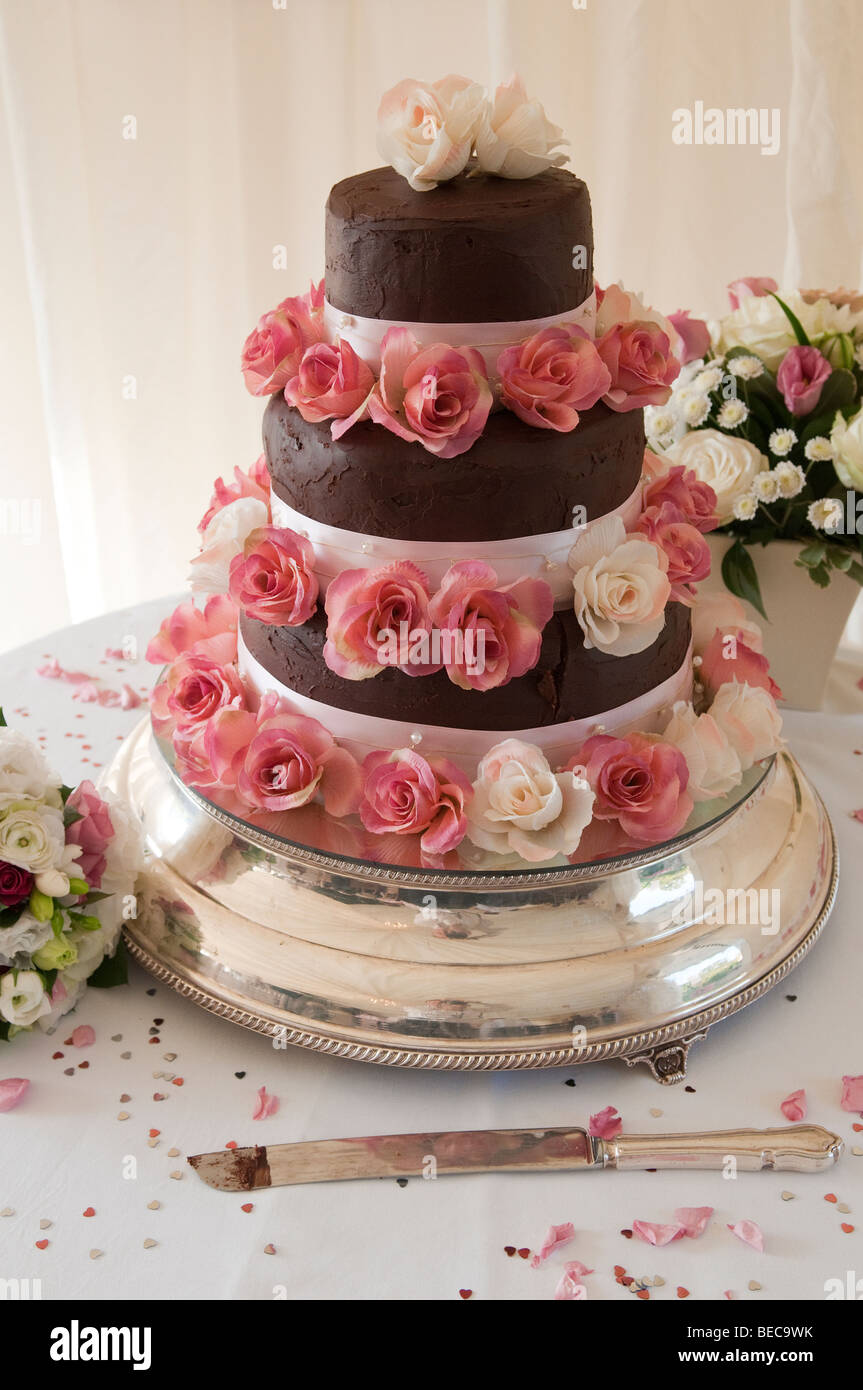 A Three Tiered Chocolate Wedding Cake With A Rose Decoration Stock