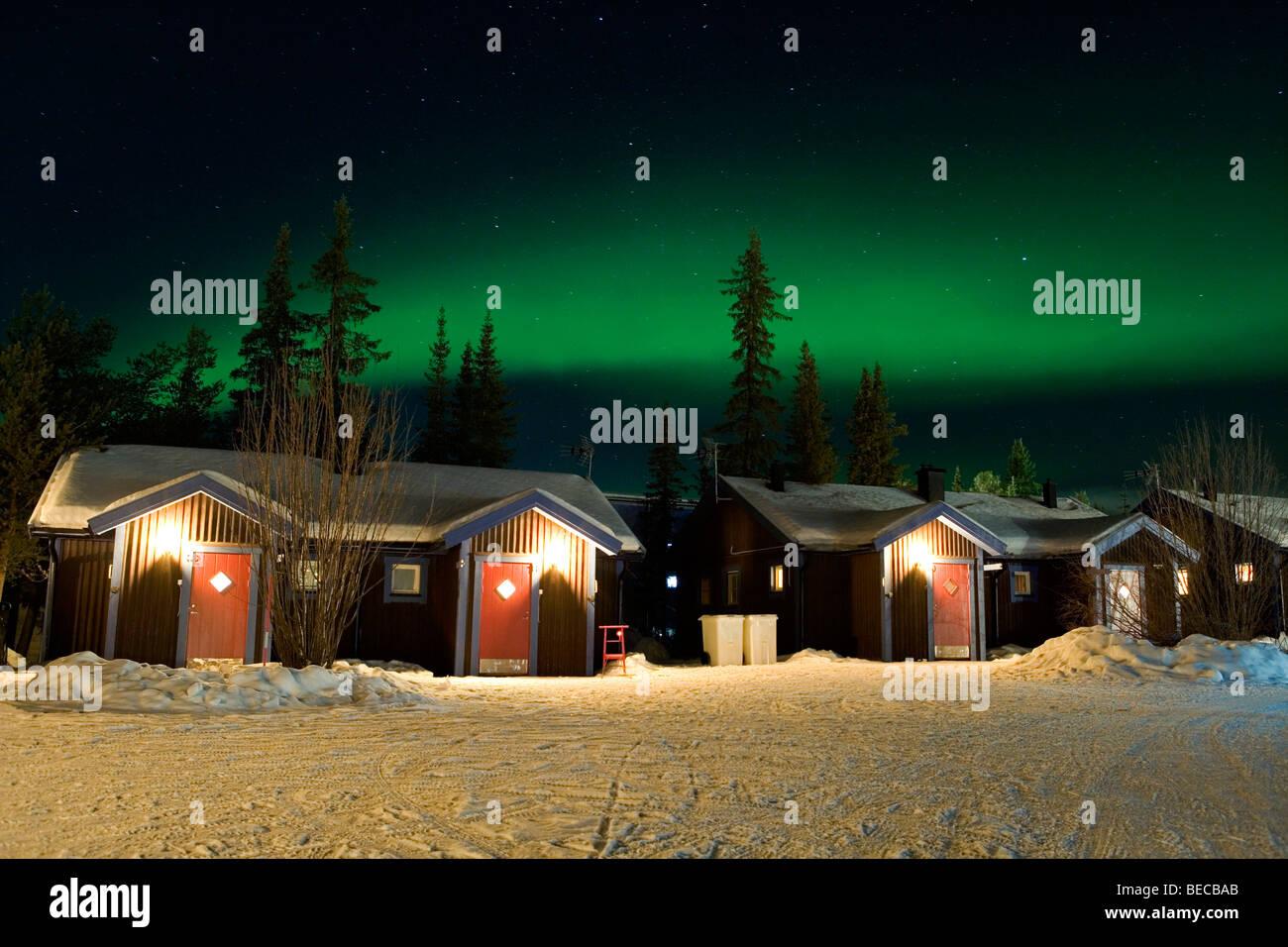 Northern lights over cabins at the Ice hotel in Jukkasjärvi, Sweden. - Stock Image