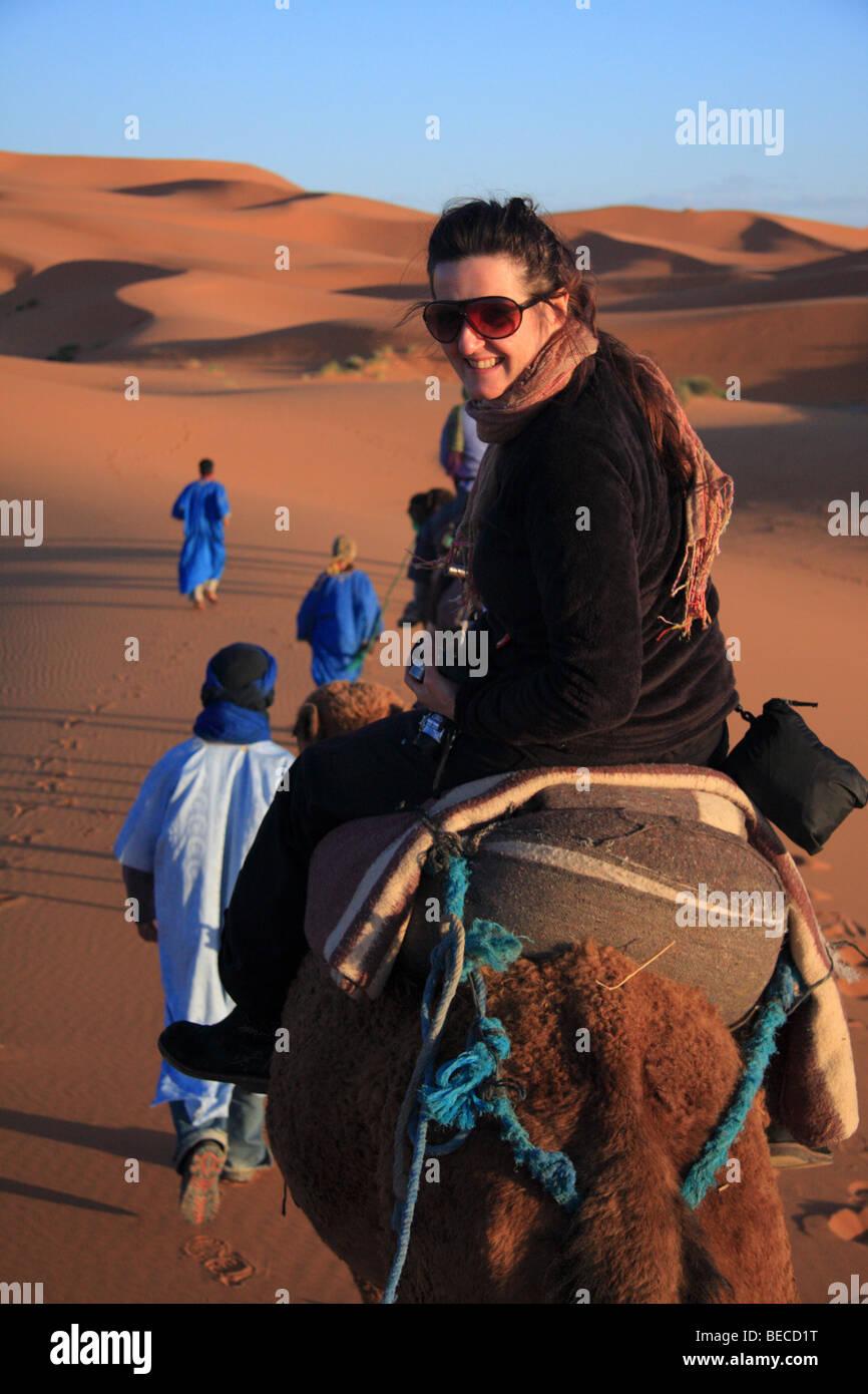 Female tourist on a camel trek led by blue men crosses Erg Chebbi sand dunesin the Sahara desert near Merzouga, Stock Photo