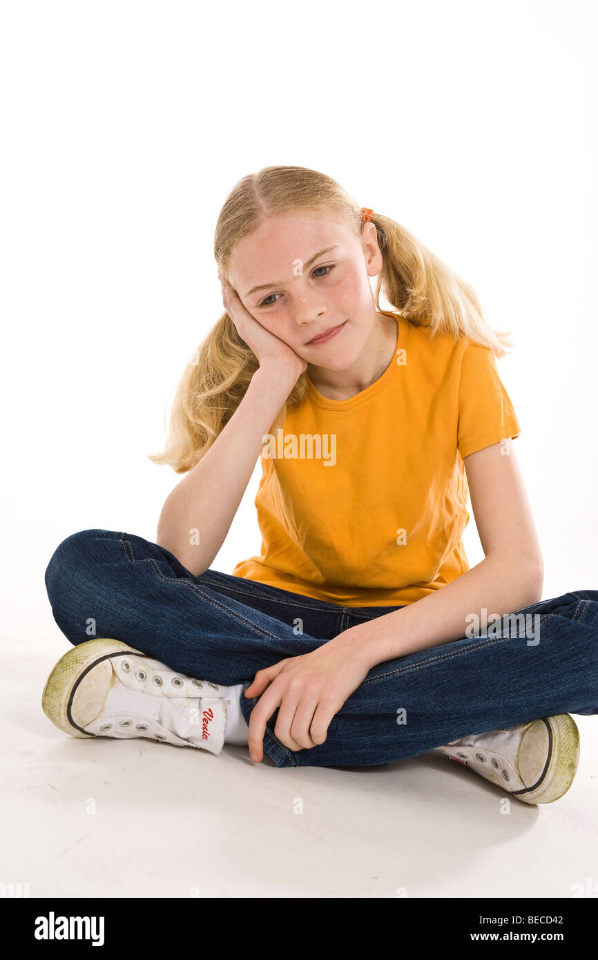 A sad, blonde girl sitting with crossed legs - Stock Image