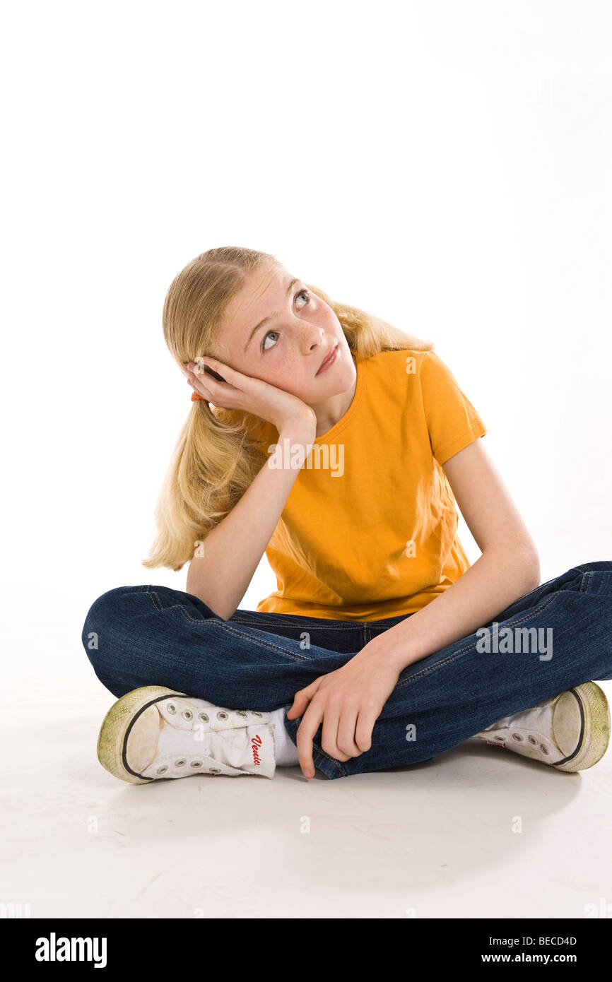 A pensive, blonde girl sitting with crossed legs - Stock Image