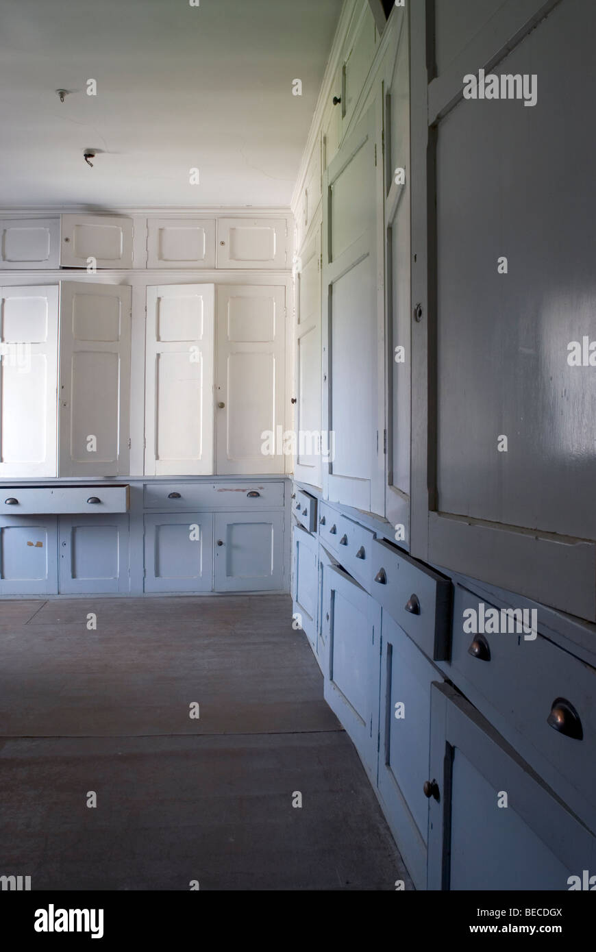 Disused  bedlinen room with  white and blue cupboards in old english mansion house - Stock Image