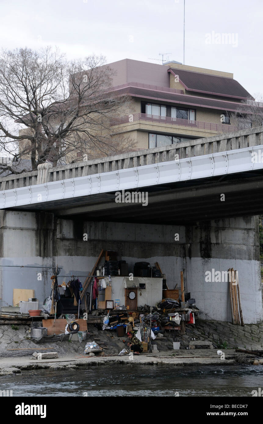 Homeless person under a bridge at the river Kamo in Kyoto, Japan, Asia - Stock Image