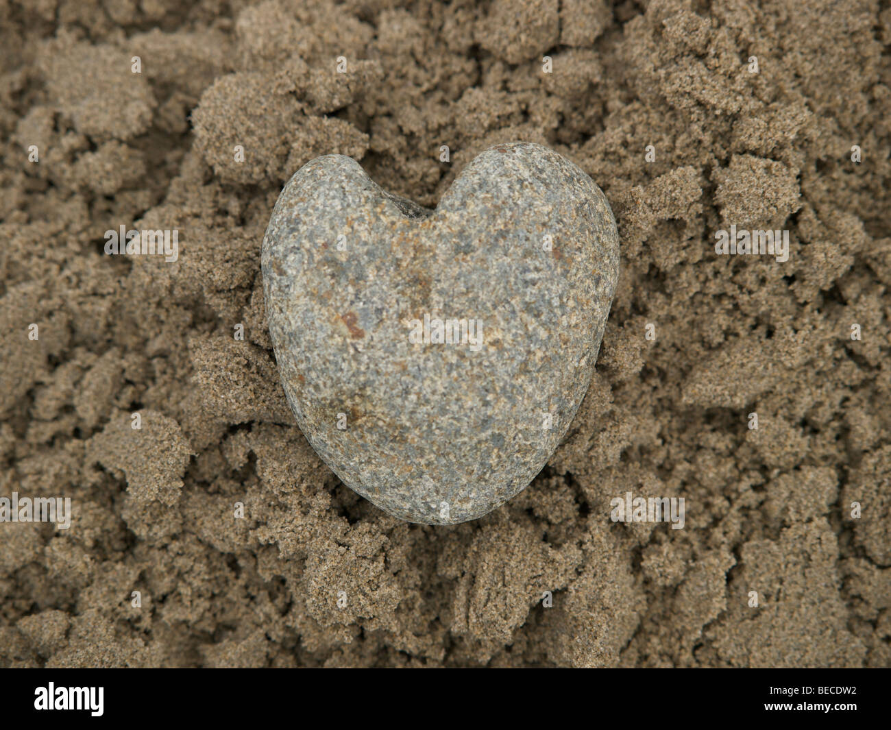 Heart of stone lying in wet sand - Stock Image
