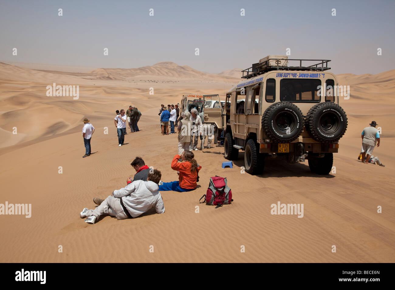 Tourists among sand dunes near Swakopmund, Namib Desert, Namibia, Africa - Stock Image