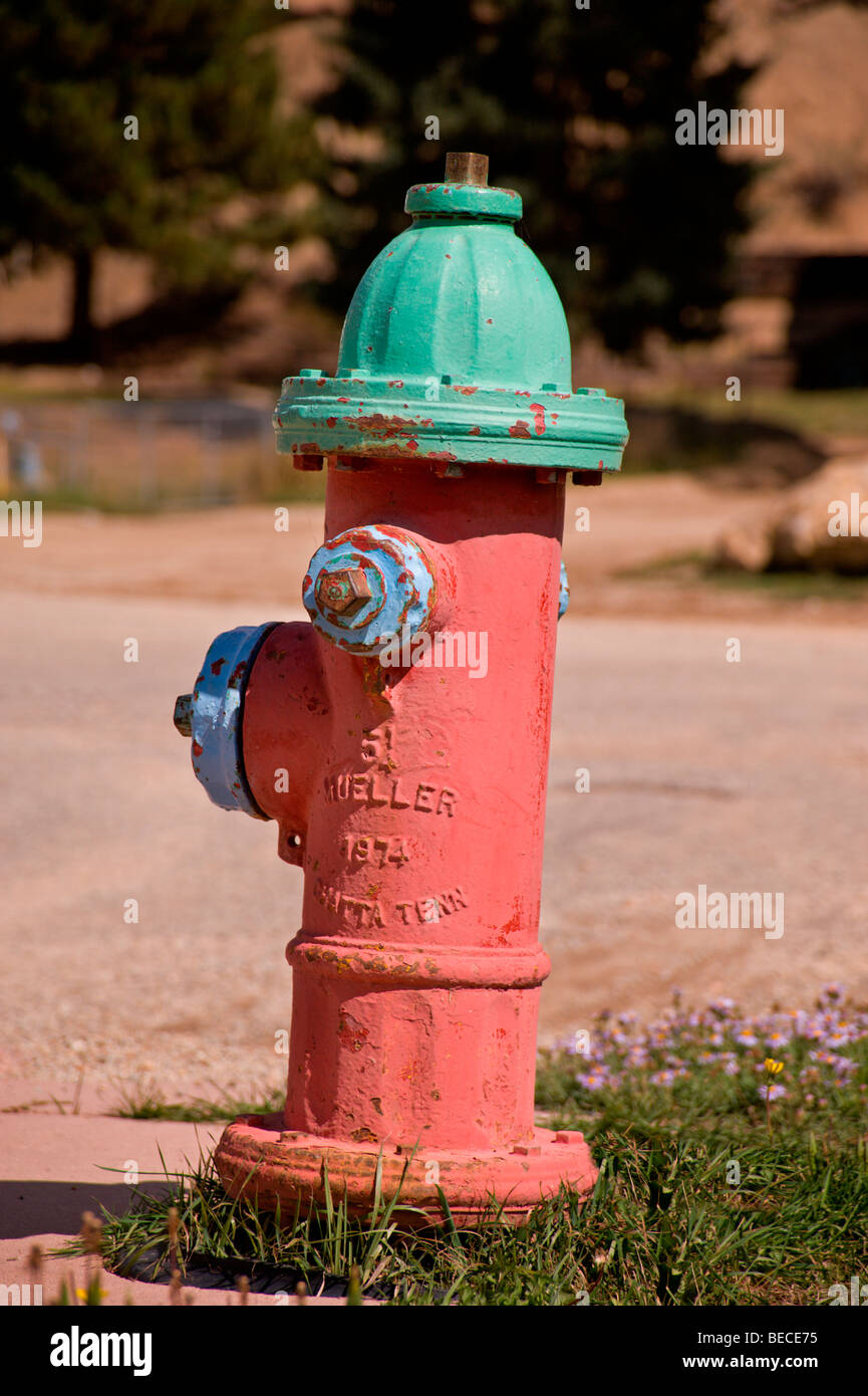 A Mueller fire hydrant, painted in festive colors, stands at the ready in Red River, New Mexico. - Stock Image