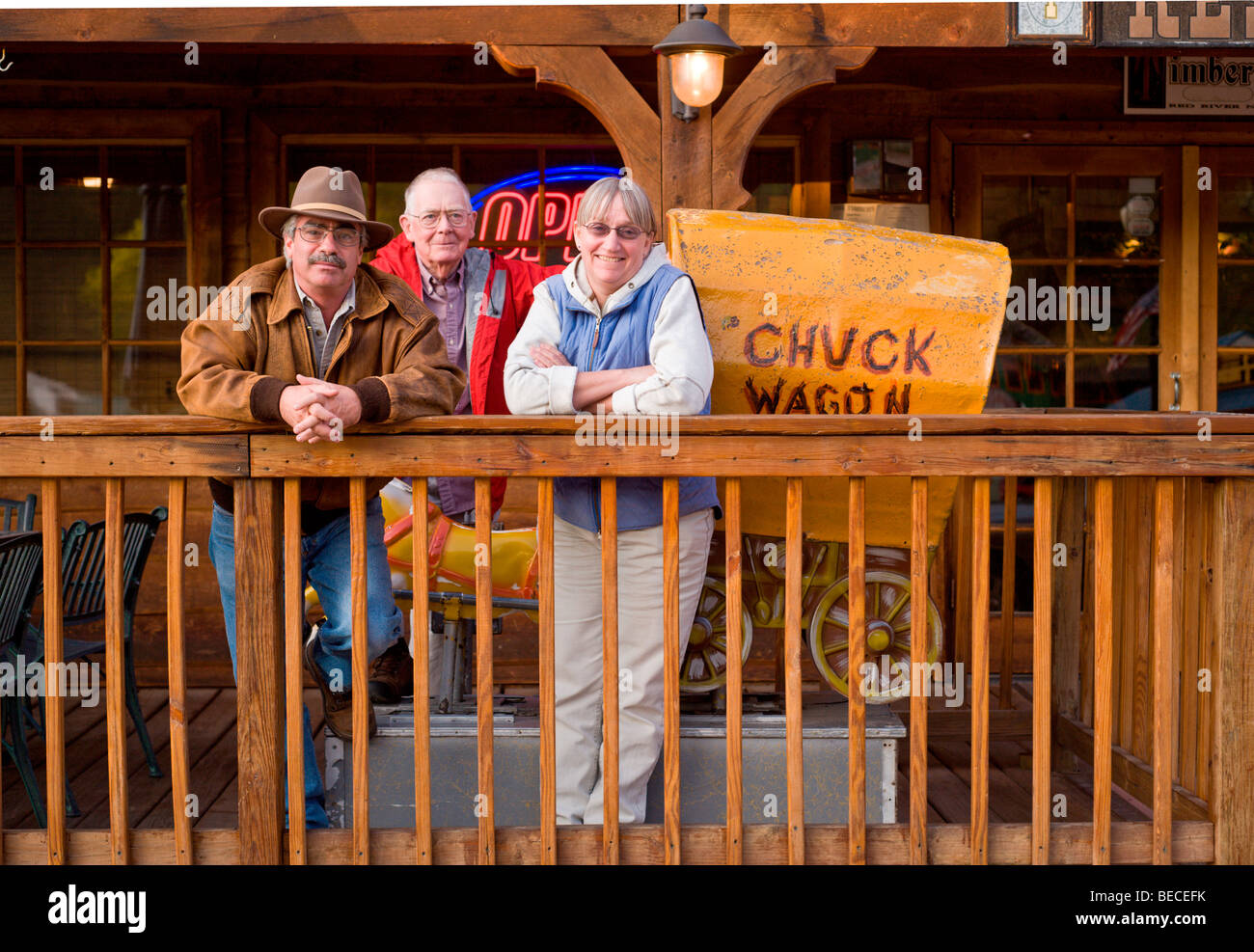 Three tourists lounge on the porch of the Timbers restaurant in Red River, New Mexico. - Stock Image