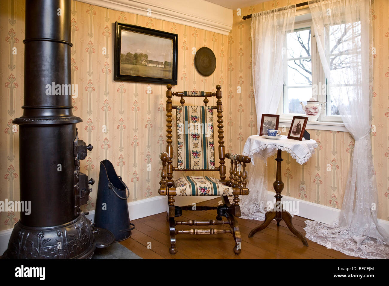 Old rocking chair at a woodburning stove - Stock Image