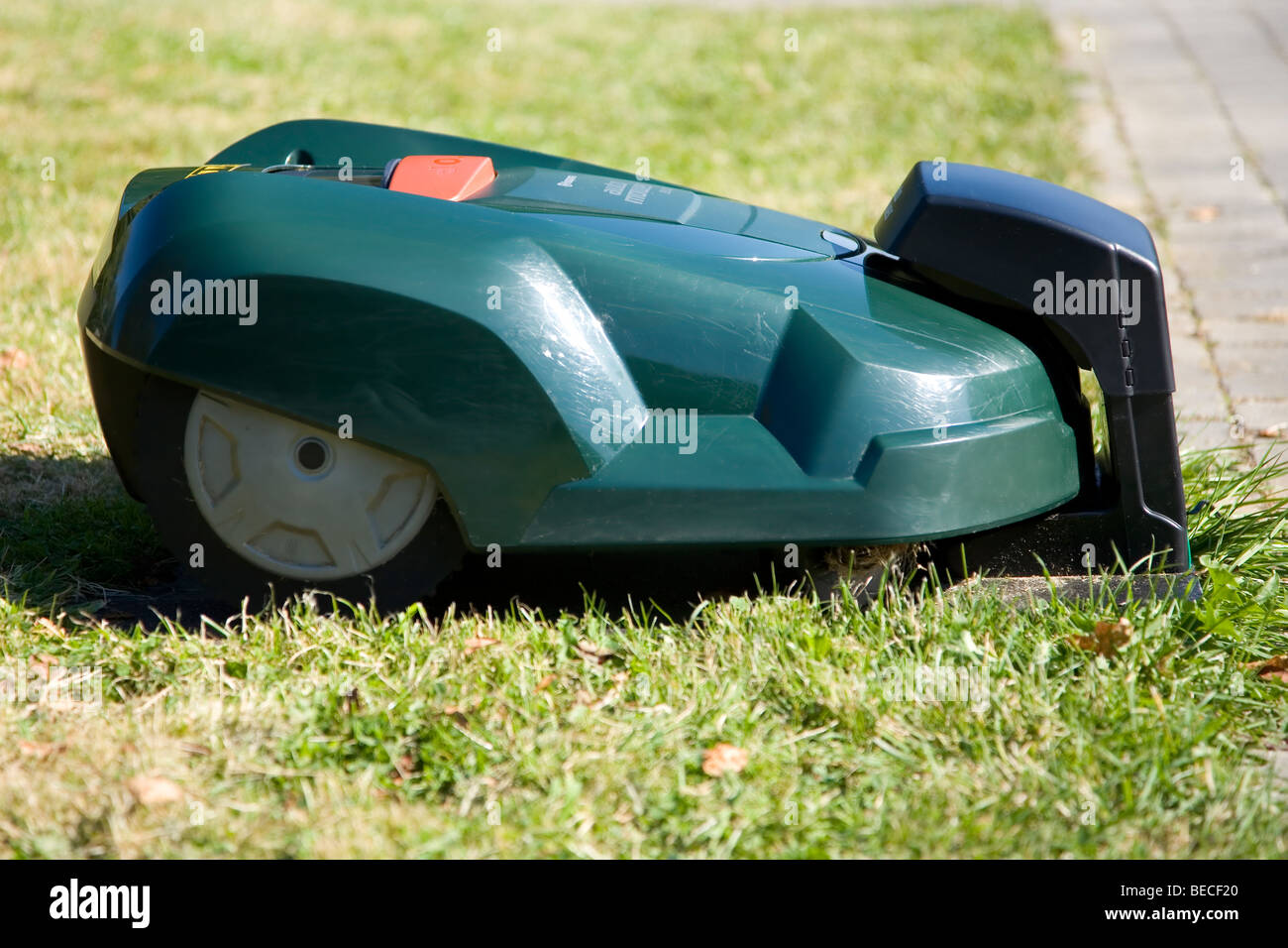 Green automatic robot lawnmower docked in its charging station near a patio, side view - Stock Image