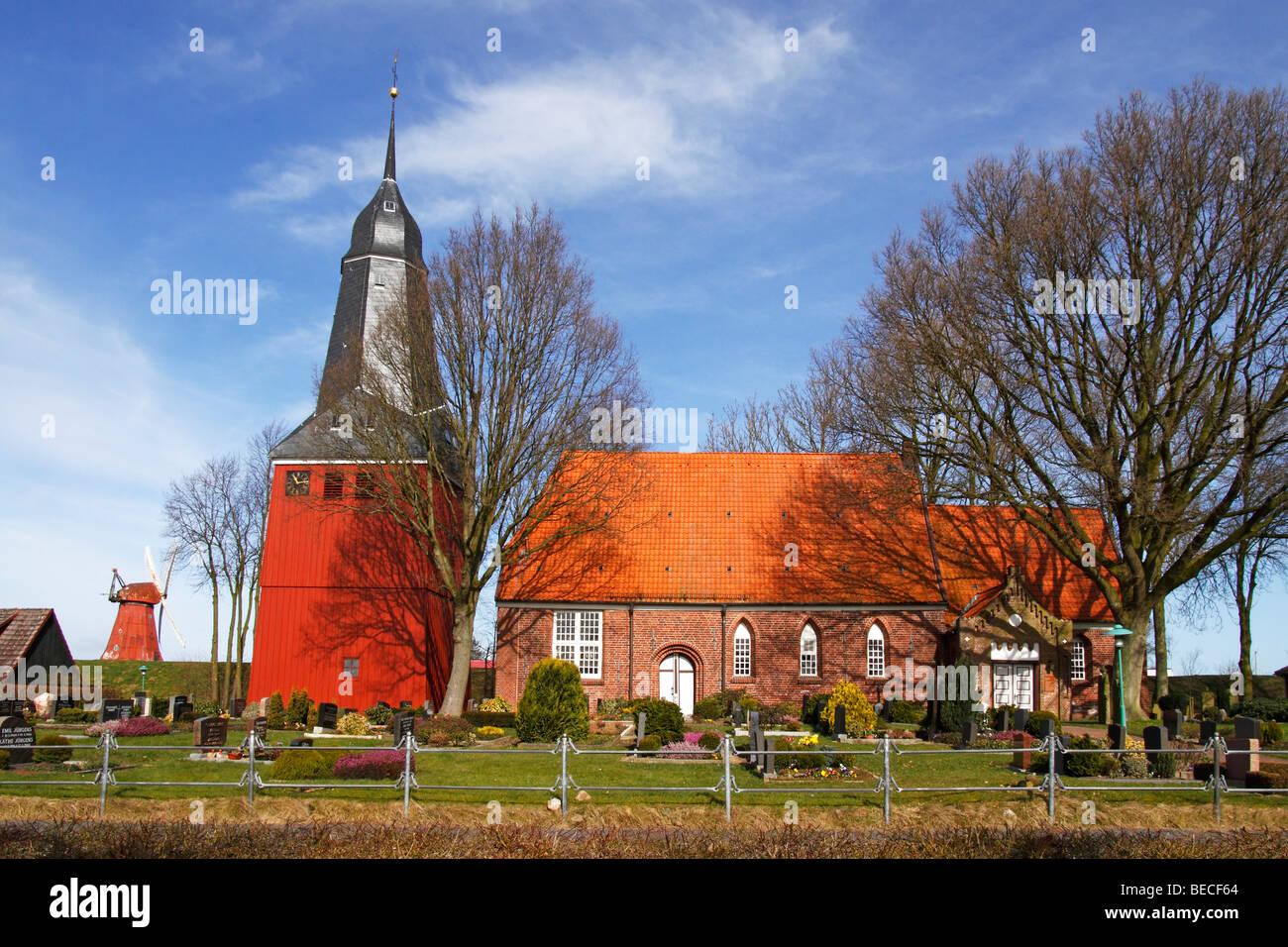 St. Nicolai-Kirche church and old wind mill in Beidenfleth, district Steinburg, Schleswig-Holstein, Germany, - Stock Image