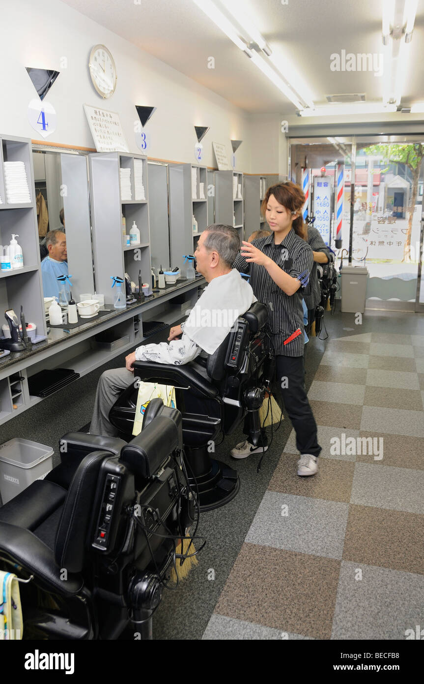 Modern hairdressing salon with easy chairs in which's backrests all tools can be stored, Kyoto, Japan, East - Stock Image