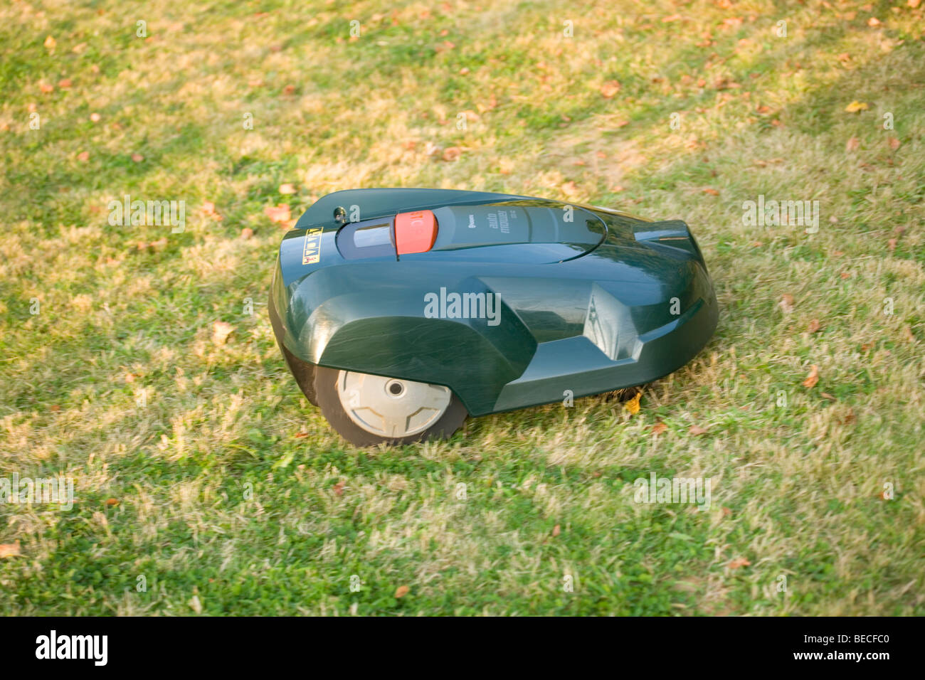 Automatic robot lawn mower cutting grass - Stock Image