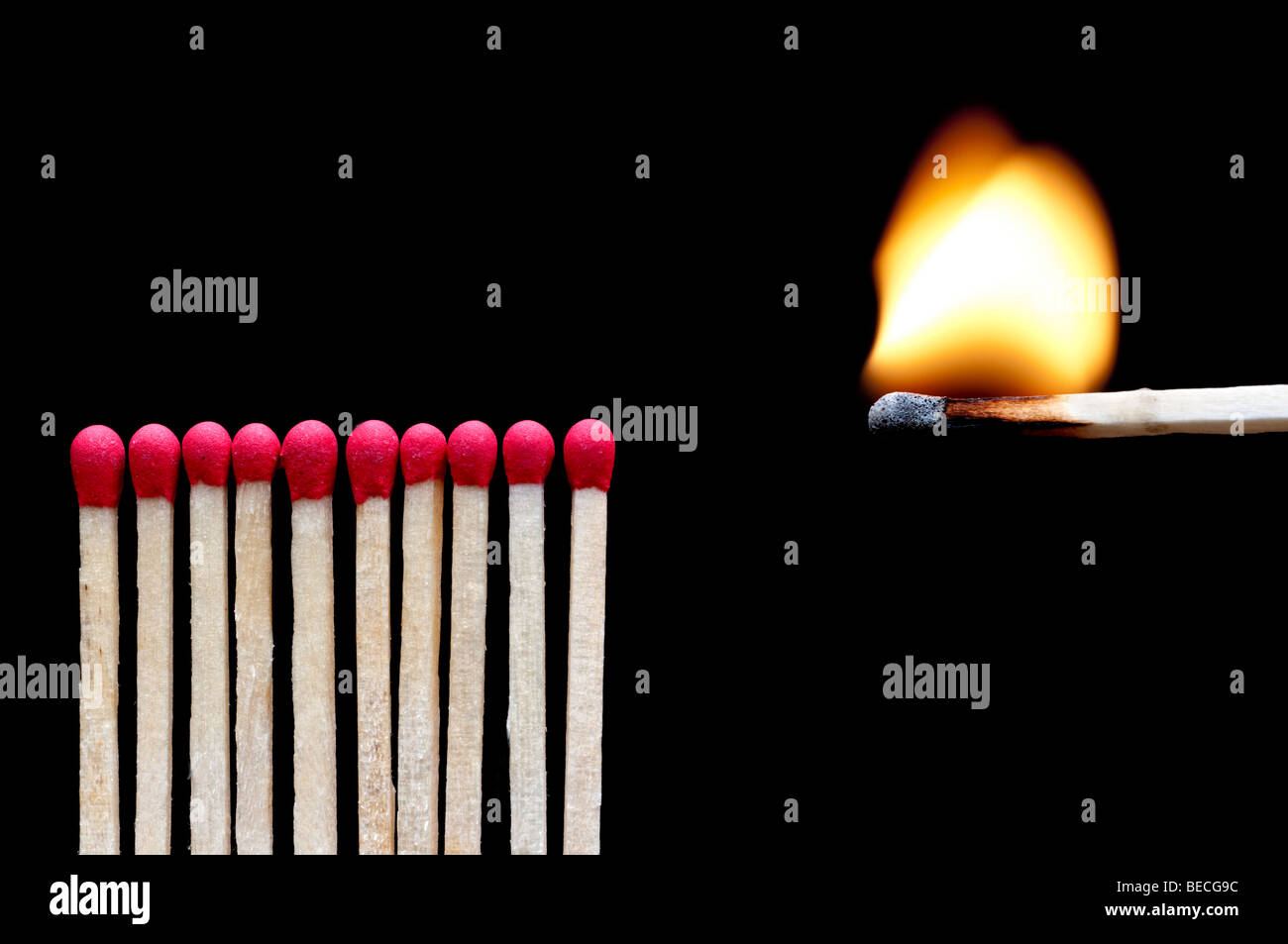 A burning match near other matches on black - Stock Image
