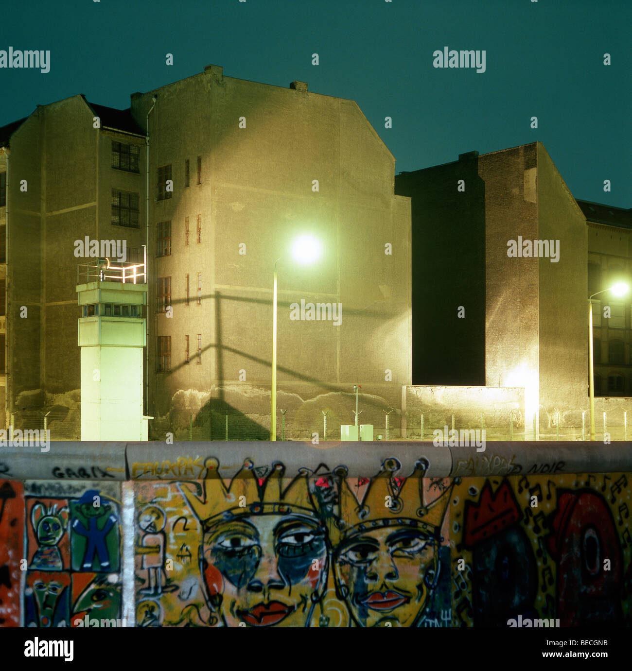 Berlin Wall with graffiti, guard tower and illuminated no man's land in the back, Berlin, Germany - Stock Image
