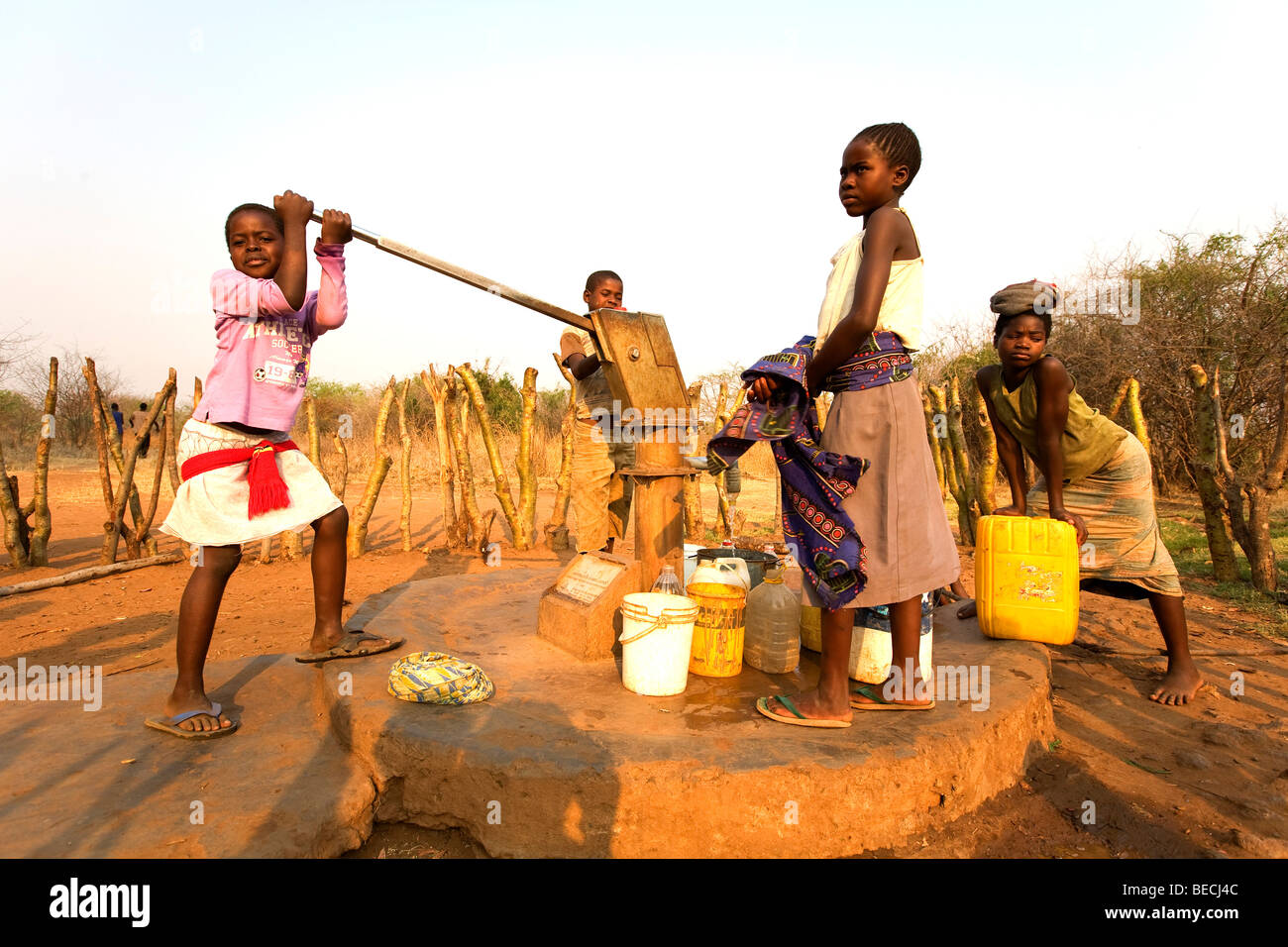 Children pumping water out of a well, African village Sambona, Southern Province, Republic of Zambia, Africa Stock Photo