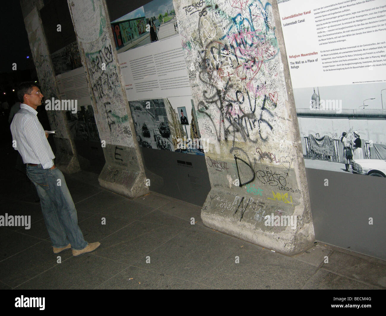 Tourist looks at an exhibition at the Berlin Wall, Potsdamer Platz, Berlin, Germany. - Stock Image
