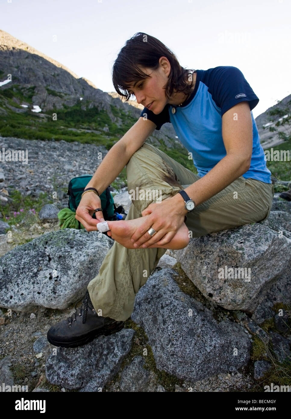 Young woman hiking, backpacking, taping blister on toe, hiker, Klondike Gold Rush National Historical Park, Chilkoot - Stock Image