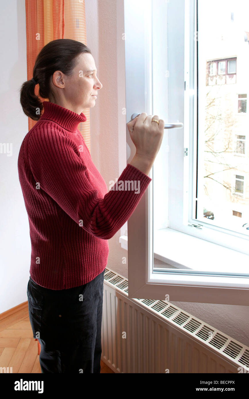 A young woman airing her apartment - Stock Image