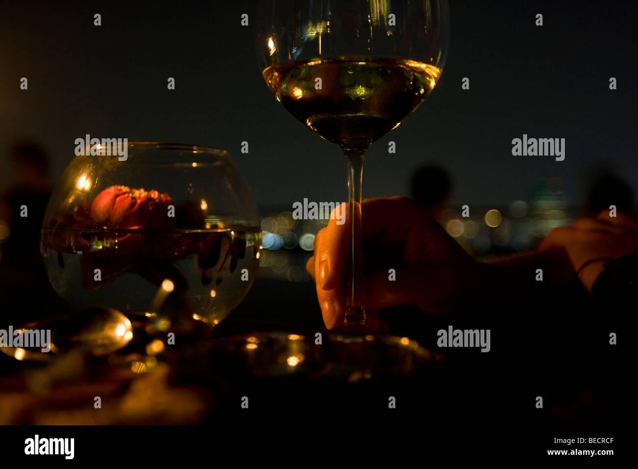 Holding a glass of white wine at Moon Bar Vertigo skybar Bangkok - Stock Image