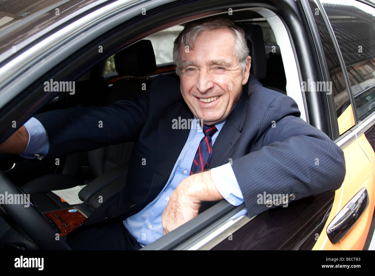 Erich Sixt, chief executive and main shareholder of the Sixt AG, sitting in a car with the Sixt logo - Stock Image