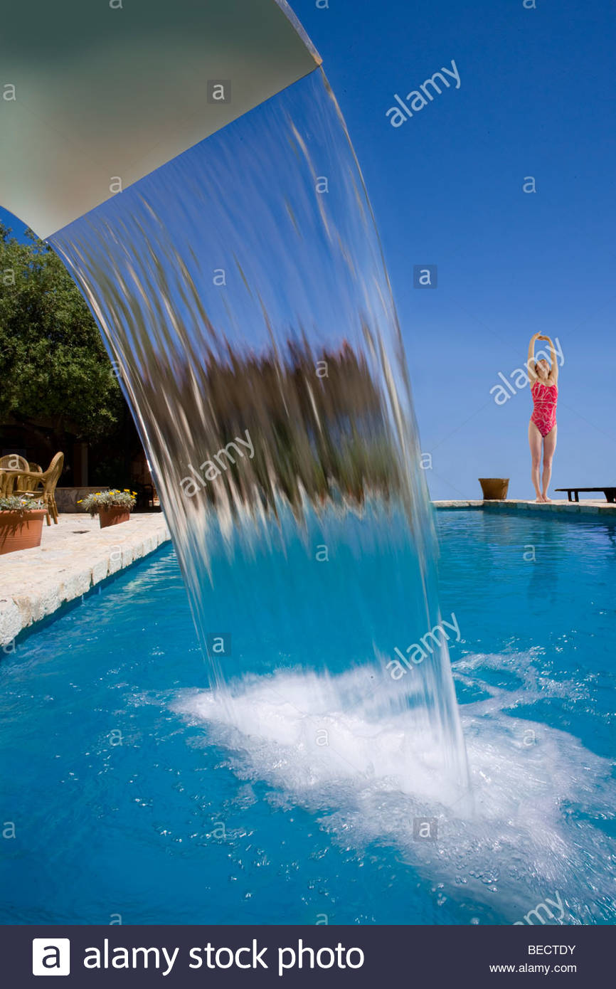 Woman in bathing suit stretching at edge of swimming pool with waterfall - Stock Image
