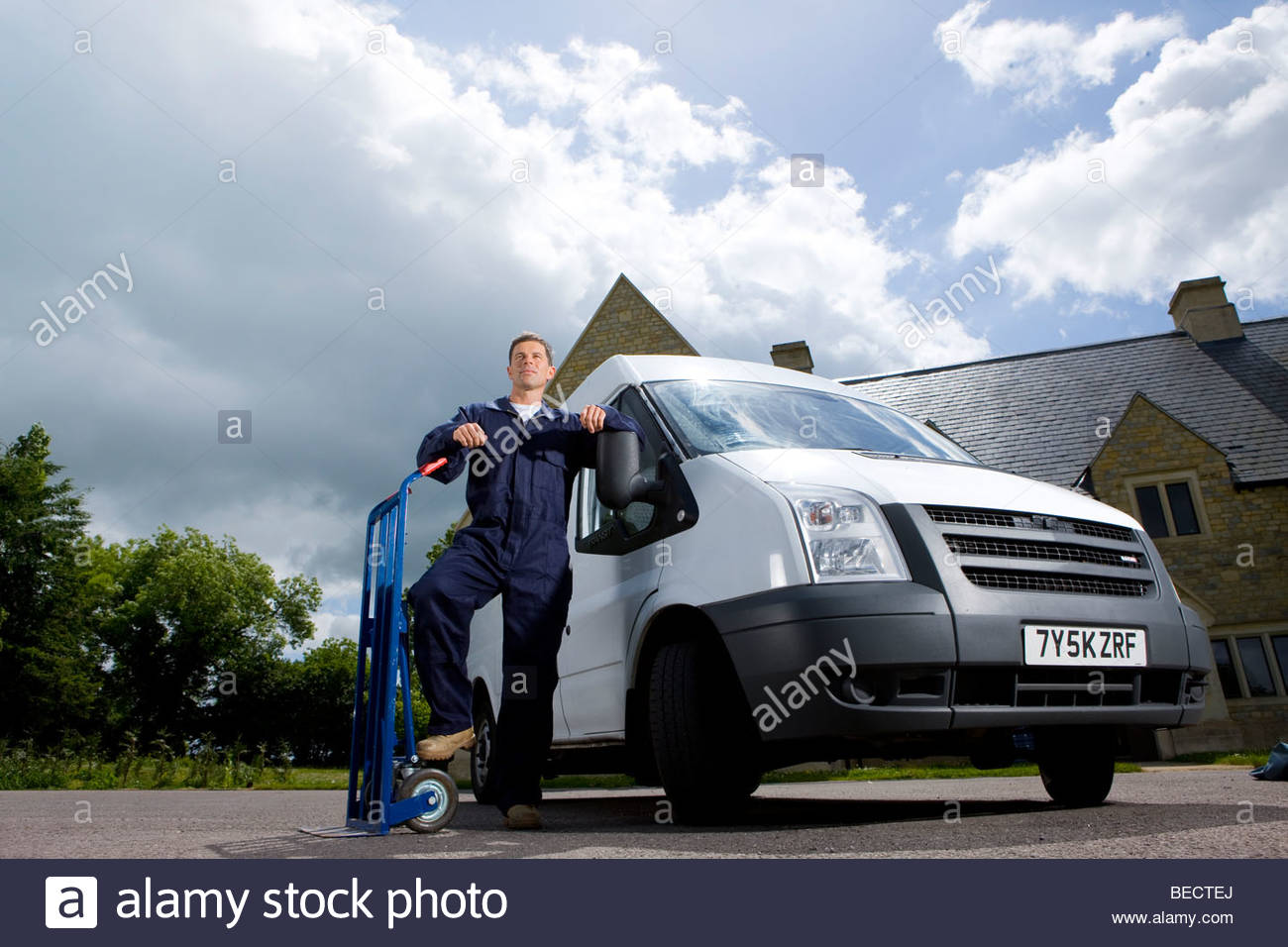Man in coveralls leaning on hand truck near work van - Stock Image