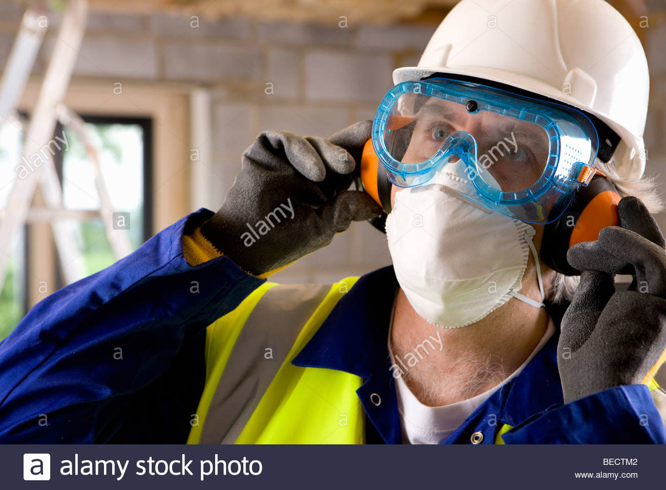 Close up of man wearing hard hat, goggles, mask and ear protectors - Stock Image