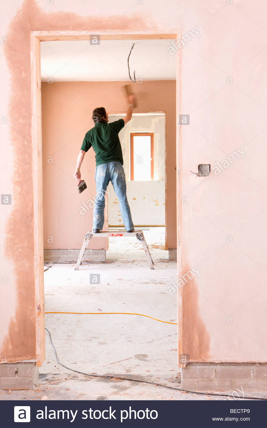 Man on step stool plastering wall in house under construction Stock Photo