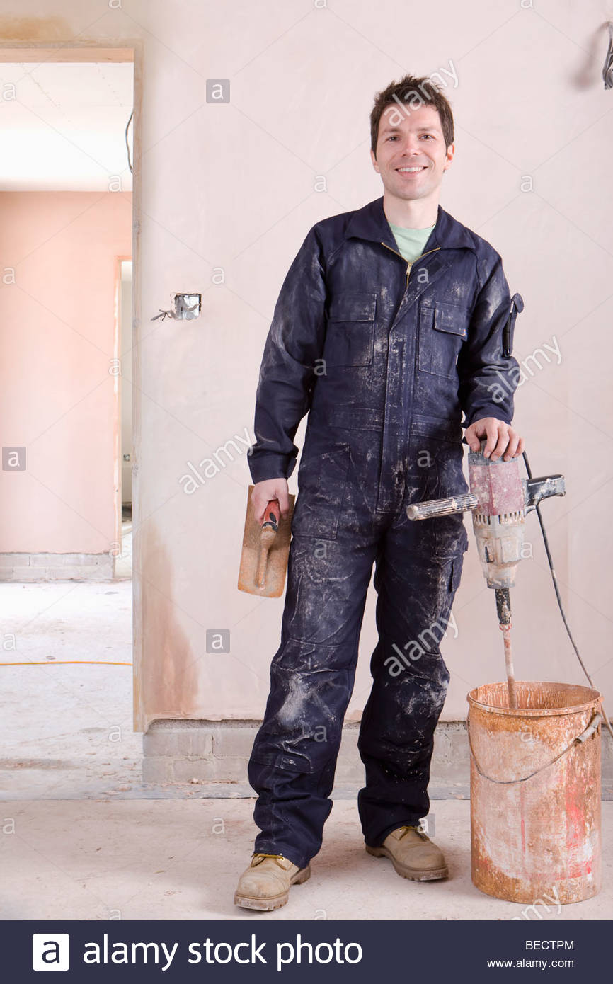 Man mixing plaster in house under construction Stock Photo