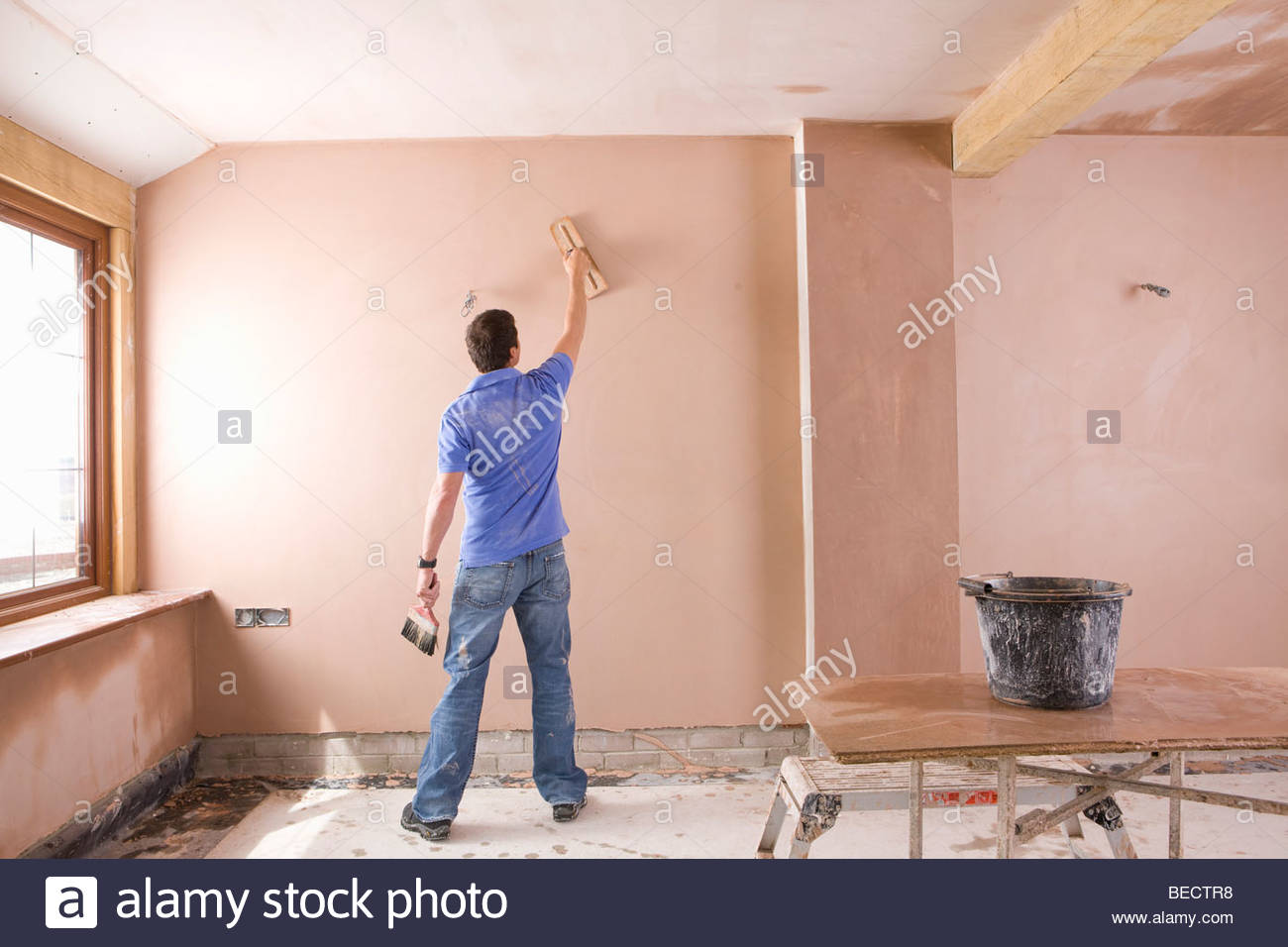 Man plastering wall in house under construction Stock Photo