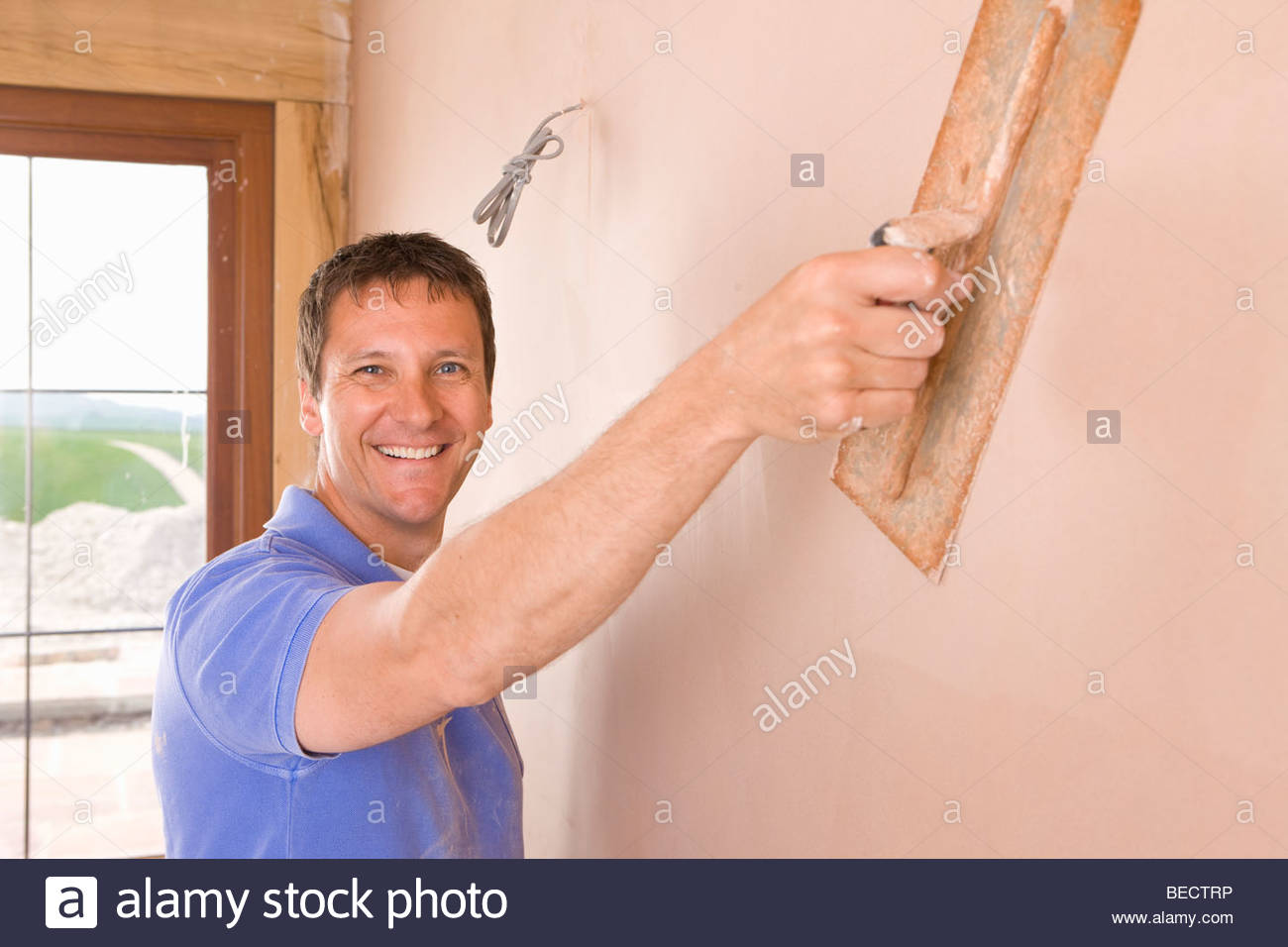 Man plastering wall with trowel Stock Photo