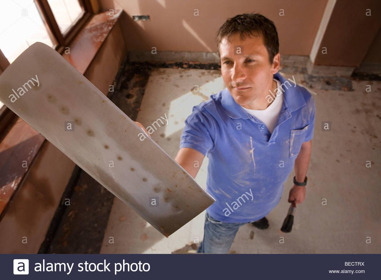 Man holding plastering trowel Stock Photo