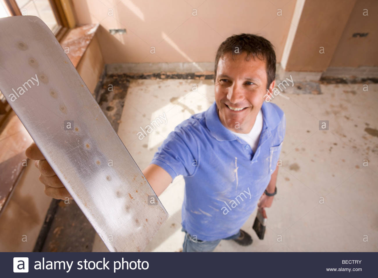 Smiling man holding plastering trowel Stock Photo