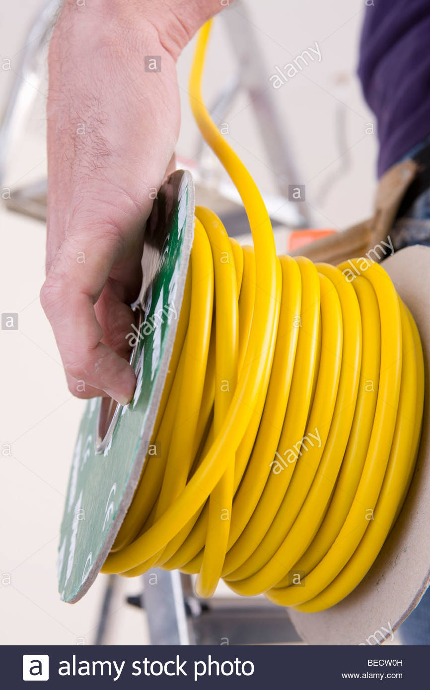 Close up of electrician holding cable spool - Stock Image