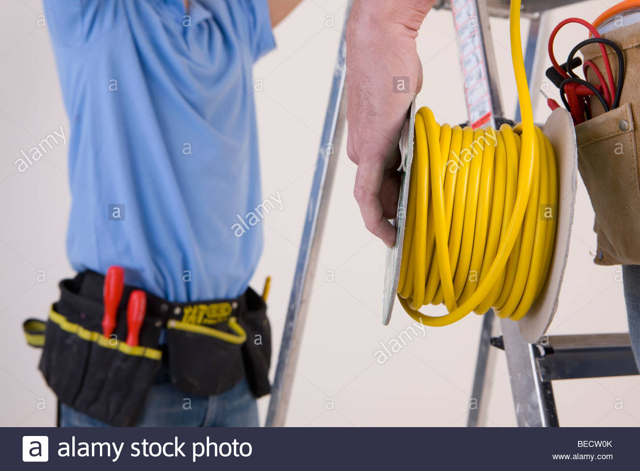 Electrician holding cable spool - Stock Image