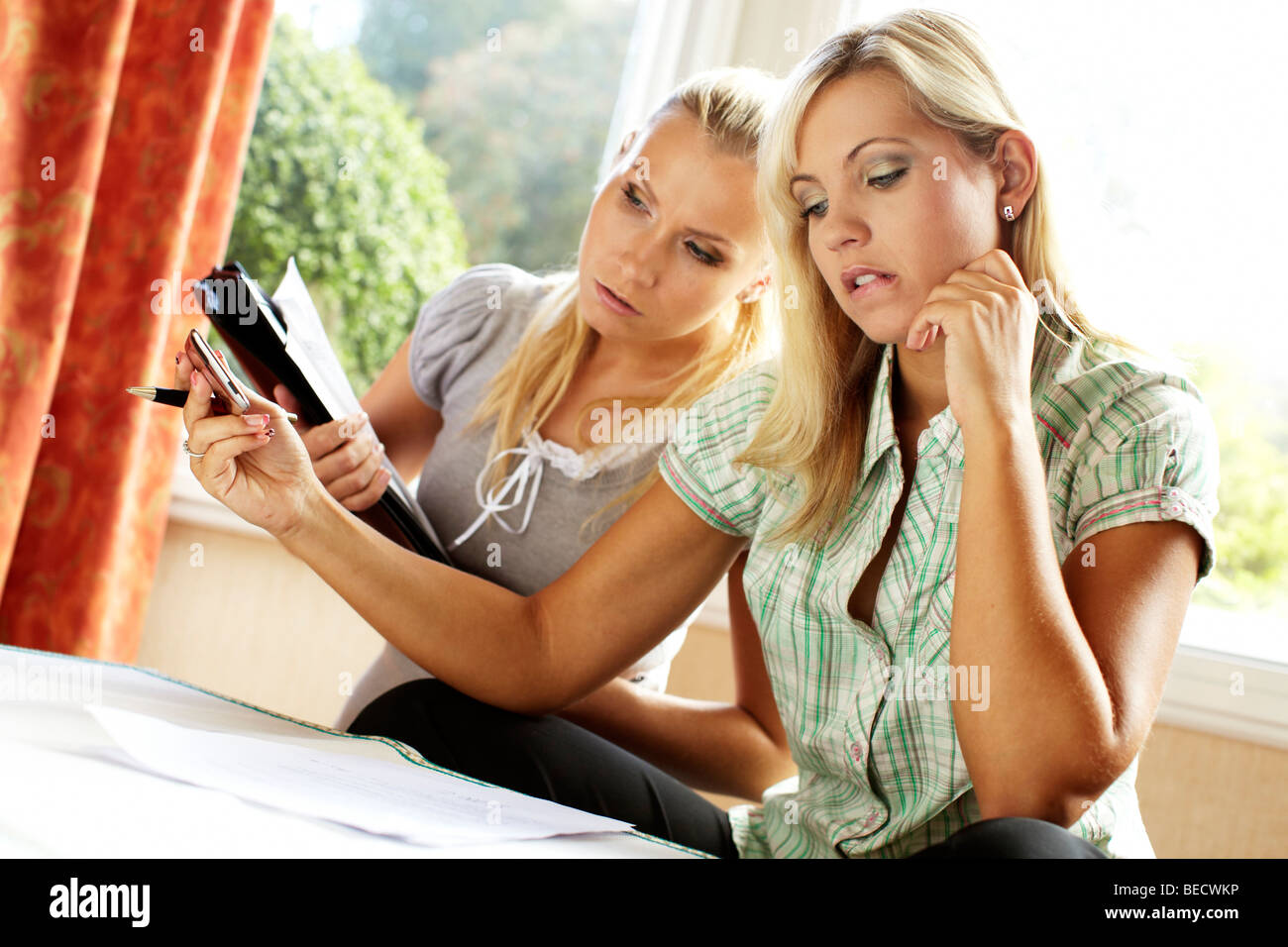 2 girls working out finances - Stock Image