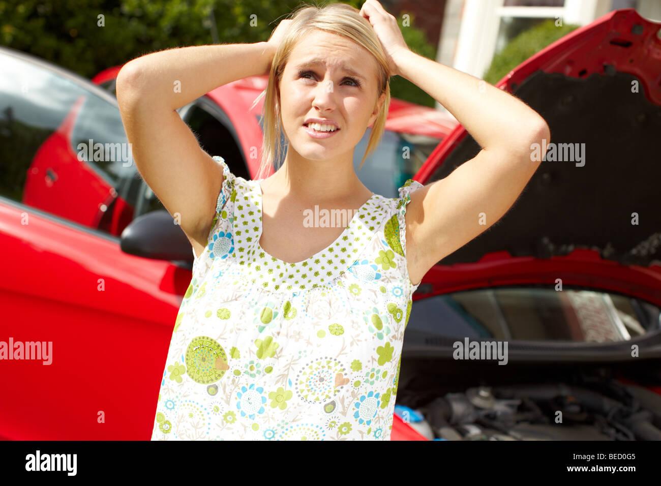 Worried girl with broken down car Stock Photo