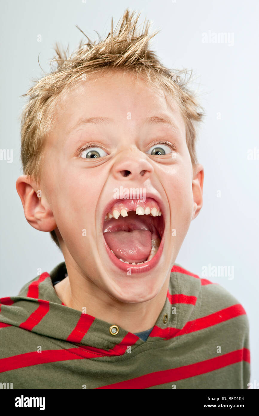 Portrait of a 7-year-old boy with a tooth gap pulling a face - Stock Image
